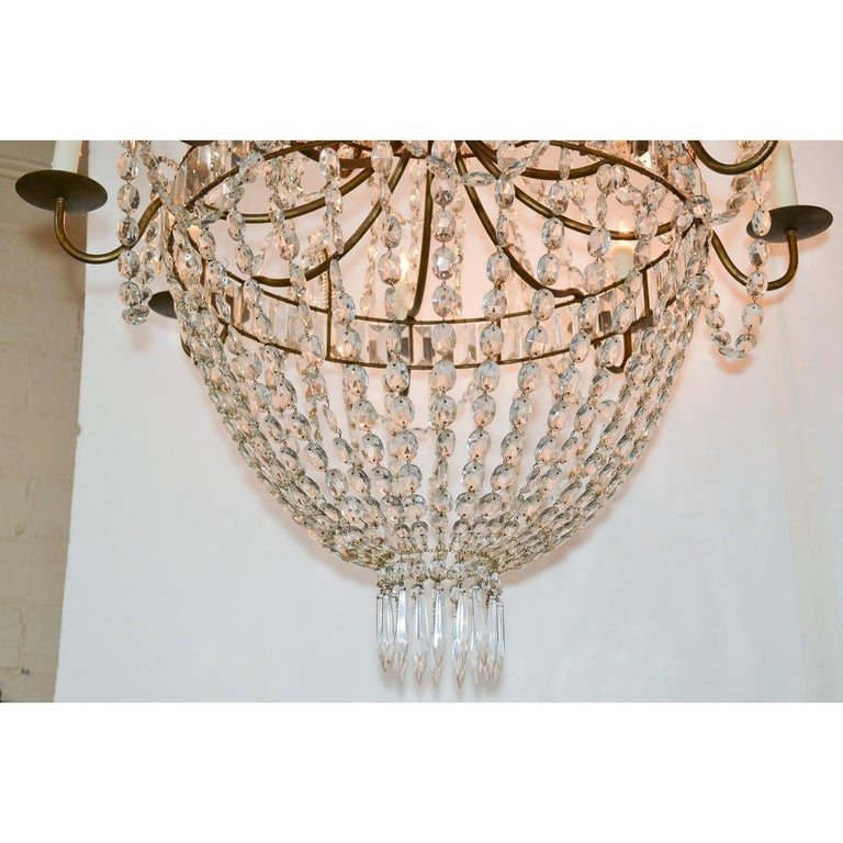 Gorgeous Swedish hand-cut crystal basket form chandelier having three graduated banded tiers inset with baguette crystal prisms. Each tier draped with strands of bead cut crystals and accented with diamond-shaped prisms, and icicle drops. Mounted