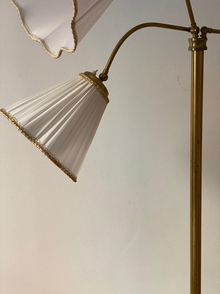 An adjustable functionalist floor lamp. Designed and produced in Sweden, 1940s. With brand new lampshades.