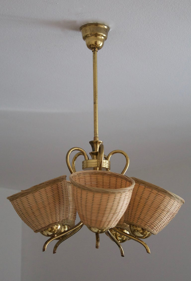 A chandelier, designed and producec in Sweden. c. 1950s. Assorted vintage rattan lampshades.
