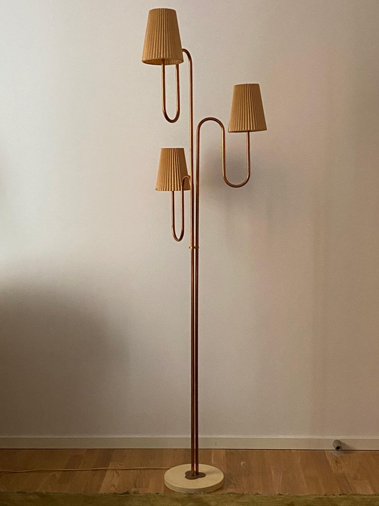A large modernist 3-armed floor lamp. Produced in Sweden, circa 1950s-1960s. In copper and cream color lacquered metal. With original paper screens. 