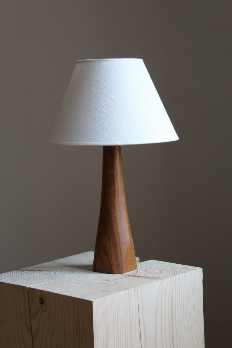 A table lamp. Designed and produced in Sweden, 1960s. In finely sculpted solid teak. Brand new lampshade.
