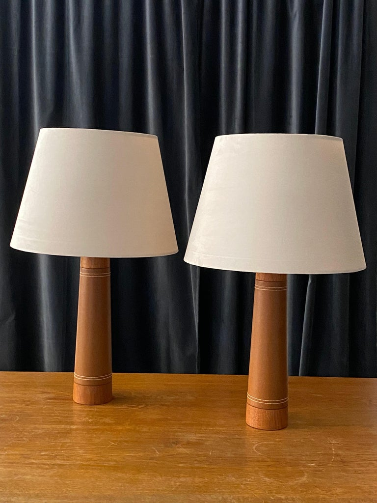 A pair of Minimalist table lamps, designed and produced in Sweden, circa 1960s. In solid sculpted teak and leatherette with contrasting stitching.   Lampshades are attached for reference, offered without lampshades. Measurements stated are of