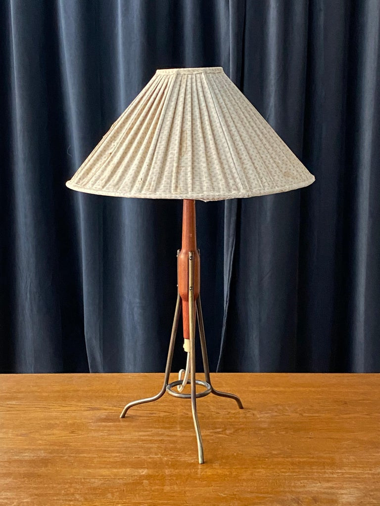 A highly modern table lamp, in teak, brass, and original beige fabric screen that needs recovering.