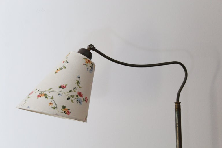 An adjustable functionalist floor lamp. With an adjustable arm. Later Swedish made lampshade.Brass and turned wood.  Dimensions variable.   Other designers of the period include Josef Frank, Paavo Tynell, Hans Agne Jacobsen, and Alvar Aalto.