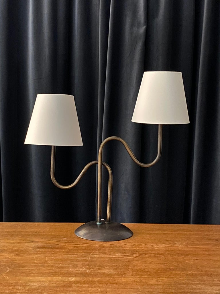 A two armed organic table lamp. By an unknown Swedish designer and maker. In brass.   Lampshades, on bulb-clips, are attached for illustration. Work is sold excluding lampshades. Dimensions stated excluding lampshades and lightbulbs.  Other