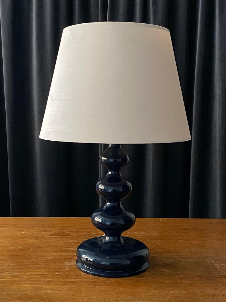 An organic freeform table lamp or desk light. In finely sculpted wood, in original blue lacquer.   Lampshades are attached for illustration and are not included in purchase, stated dimensions are without lampshades.  Other designers of the