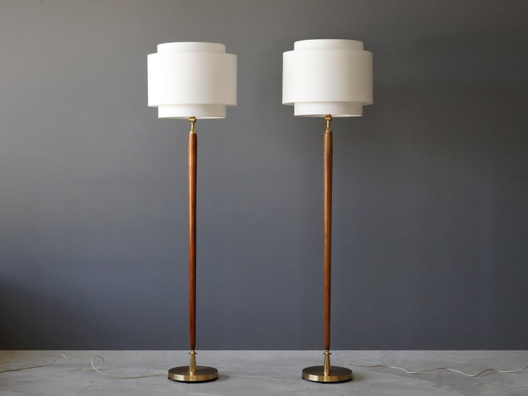 A pair of floor lamps. Designed by an unknown Swedish designer. Produced in the 1940s. Features finely carved wooden rods on brass bases. Screens are adjustable and can be tilted.   Other designers working in similar style include Paavo Tynell,