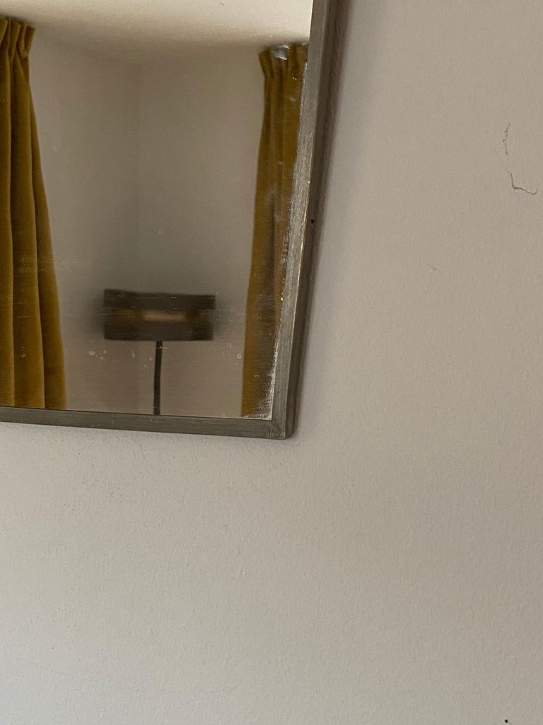 A small wall mirror. Designed and produced in Sweden, 1930s. In pewter, original mirror glass.