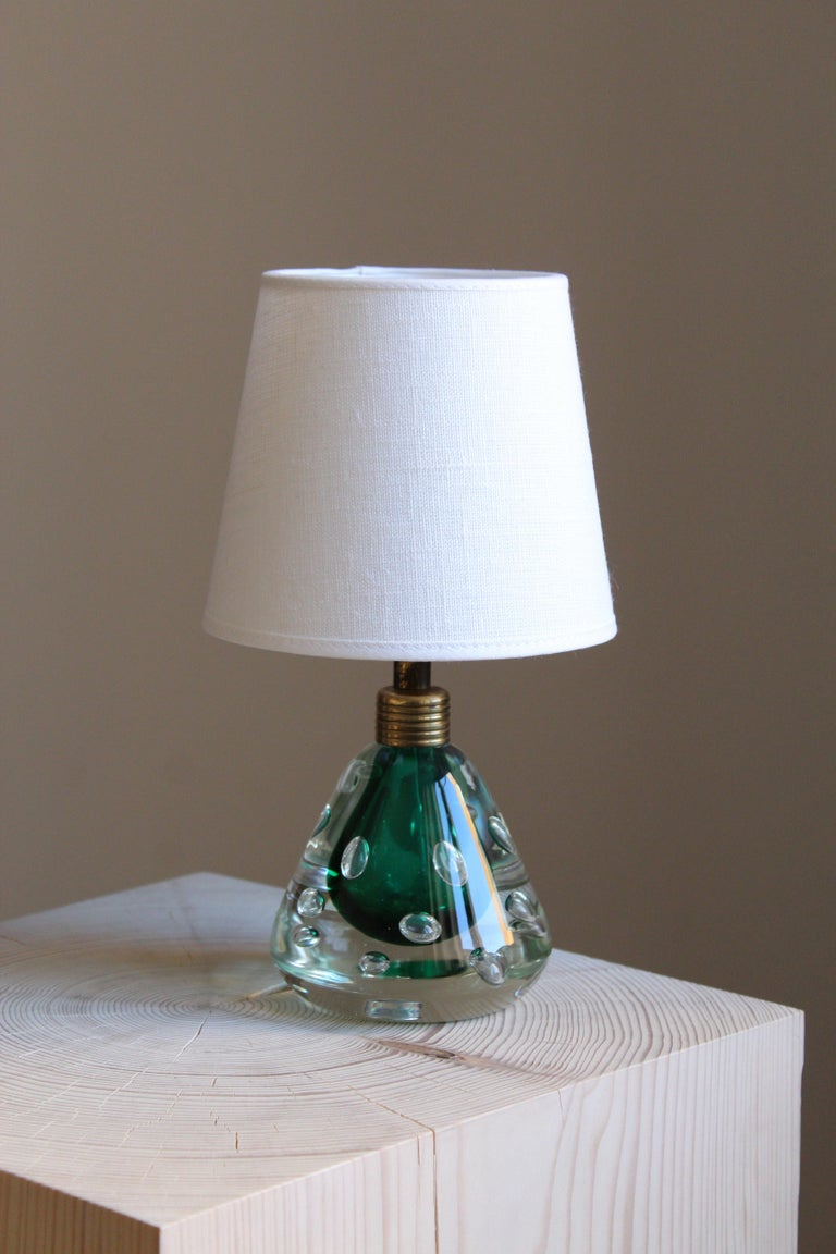 A table lamp in artisticly blown colored glass. Brass fittings. Brand new high-end lampshade in Linen.  Other designers of the period include Josef Frank, Carlo Scarpa, Venini.