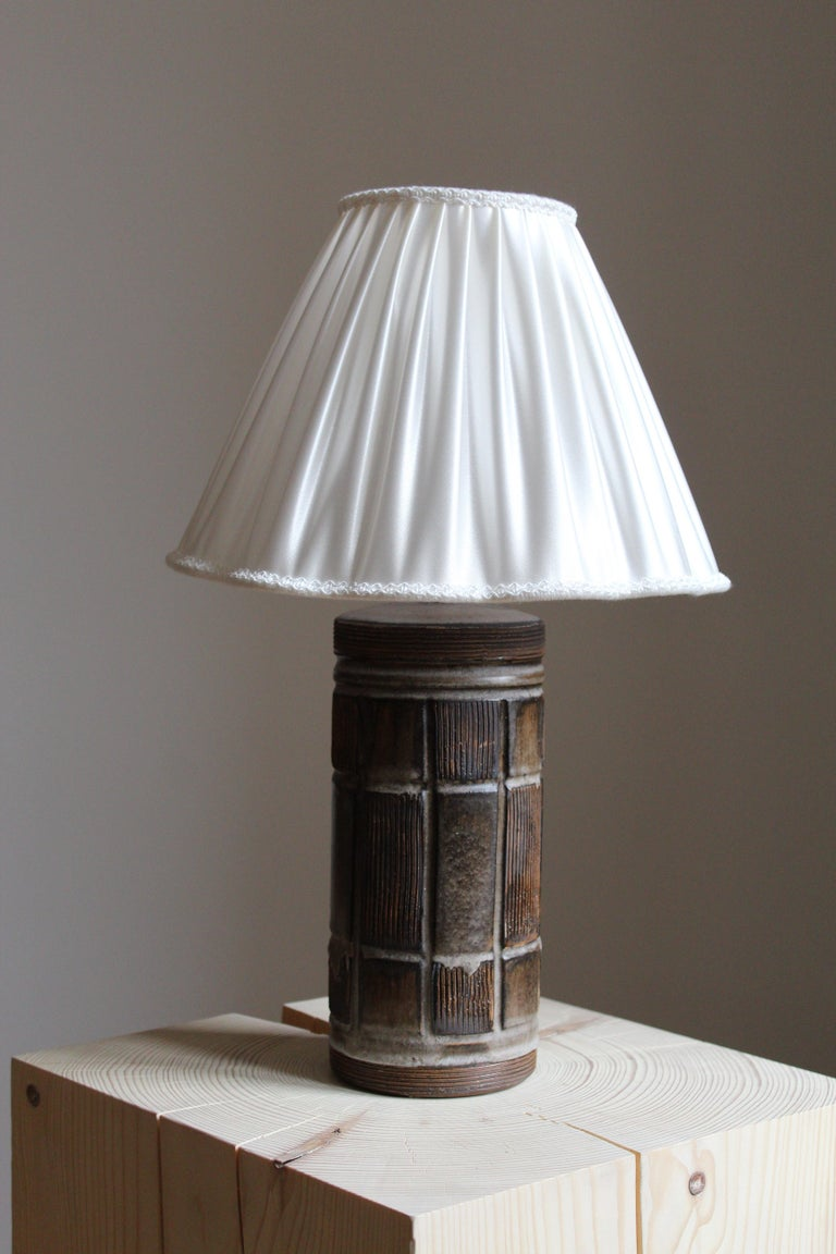 A round table lamp. In glazed stoneware with relief motifs. Unsigned  Sold without lampshade, stated dimensions exclude lampshade.  Other designers of the period include Wilhelm Kåge, Stig Lindberg, Axel Salto, Arne Bang, and Carl-Harry Stålhane.