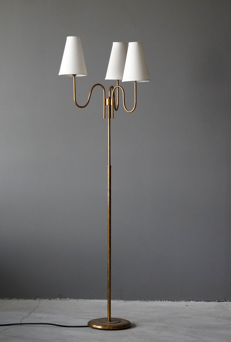 A three-armed floor lamp. By an unknown Swedish designer and maker. In brass. 