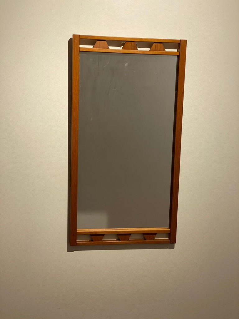 A pair of stained oak mirrors, with ornamented details. By an unknown Swedish designer. Produced in the 1950s.   Other designers of the period include Hans Wegner, Josef Frank, Finn Juhl, and Arne Jacobsen.