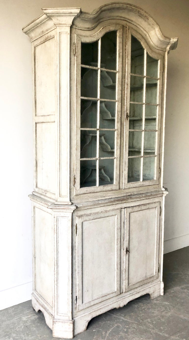 Swedish early 18th century period Rococo Vitrine cabinet in two parts with arched pediment over original glazed panel doors with multiple unusual bracket display shelves, supported the sturdy two-door base with bracket feet. Painted in grayish