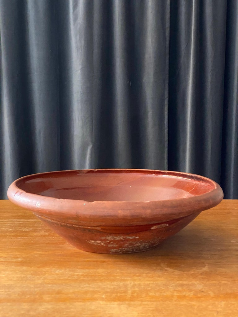 An antique and unique large organic and early farmer's ceramic pottery bowl. Produced in Sweden, 19th century.