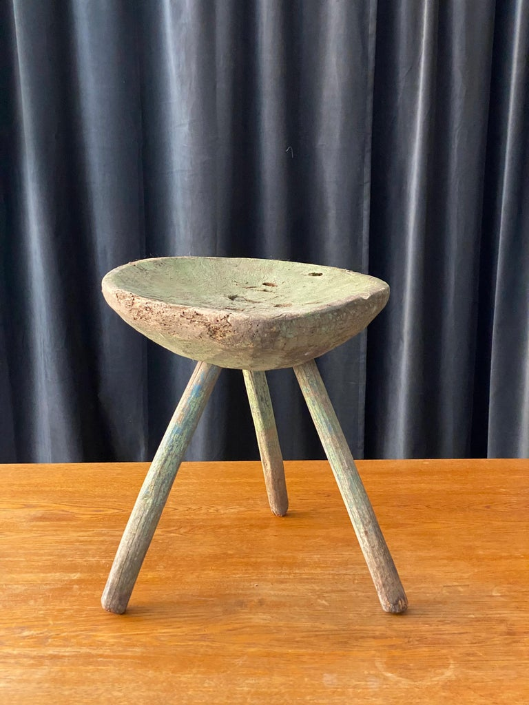 A unique organic and farmers wooden stool. Painted in green color with hints of blue. Early 19th century or possibly 18th century.  Has a very beautiful primitive sculptural appeal.