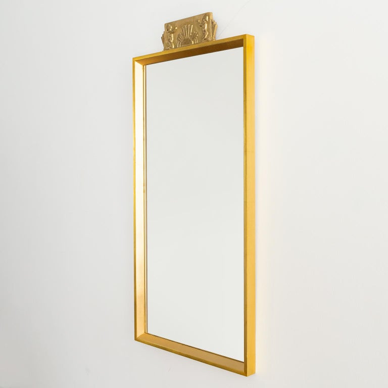 """Scandinavian Modern wall mirror with carved giltwood element showing children flanking a rising sun.   Measures: Height 39"""", width 18"""", depth 1.5""""."""