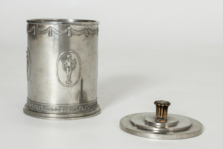 Rare, elegant pewter jar from the Swedish Grace period, made by Schreuder & Olsson. Decor of woman in different poses around the body and a Classic meandering pattern around the base. Sculpted wooden knob on the lid.
