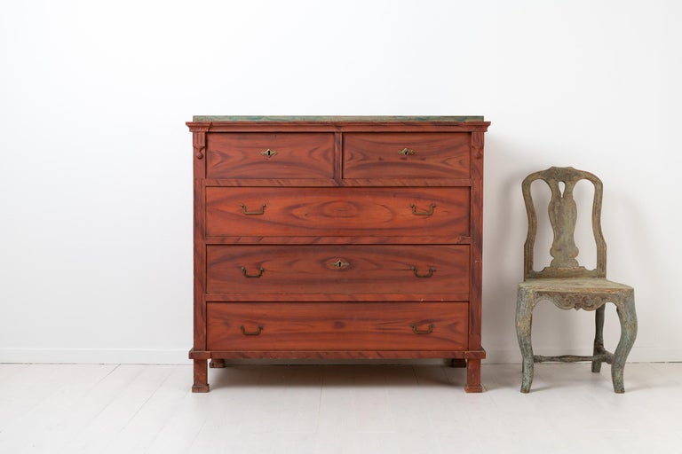 Chest of drawers from northern Sweden made during the transition time between the Gustavian and Empire period. Made between 1810 and 1820 from painted pine with original faux paint. Red frame and a blue tabletop with original hardware as well as the