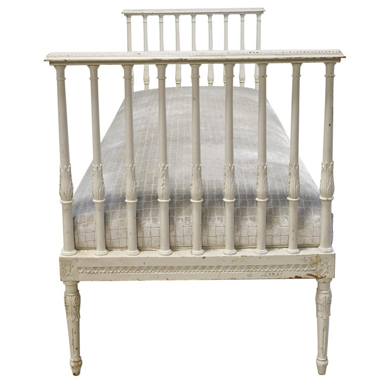 A very lovely Swedish Gustavian banquette or daybed with original, distressed white-grey paint, resting on six turned and reeded legs with carved acanthus on knees and rosettes on corner blocks and ball-and-dart carvings on apron. The sides, which