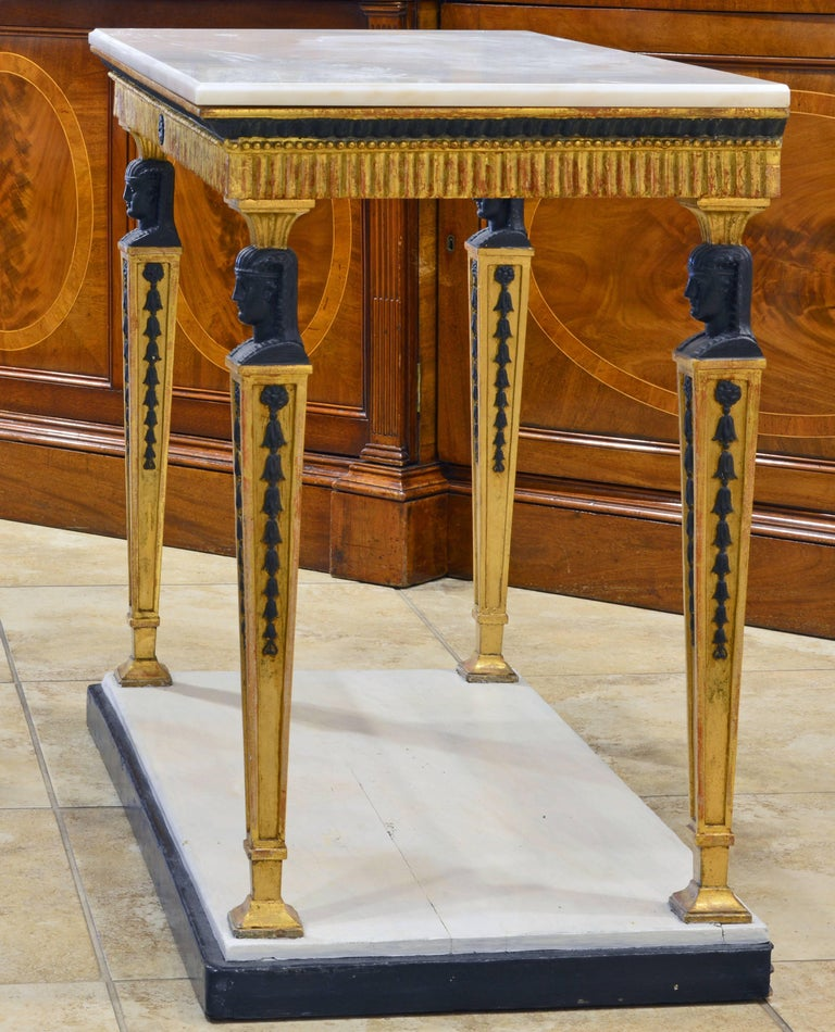 This refined Gustavian console table dating to the early 1800s features a white marble top with molded edge above a carved gilt-wood frieze finished on three sides and supported by four square tapering legs surmounted by ebonized pharaonic busts,