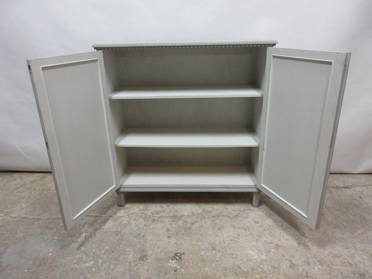This is a 2-door Swedish Gustavian fluted door sideboard. This cabinet has been restored and repainted with milk paints