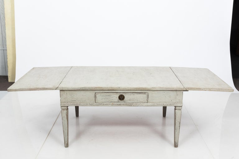 Unique Gustavian Style coffee table with drop leaves, made in Sweden circa 1850. The table is painted white with lovely patina from age. Decorated simply with beaded trim and sits on plain tapered legs. This versatile piece was likely a dining table