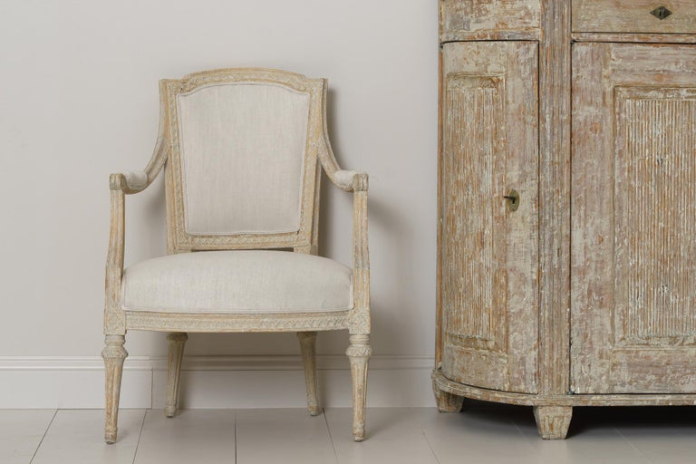 A Swedish period Gustavian armchair signed IEH by Erik Höglander (1750-1813) from Stockholm. This beautifully made chair has been hand-scraped to reveal the original paint and has been newly upholstered in linen. The seat height is 16.57 inches.