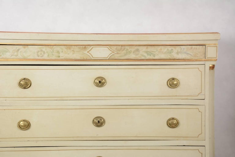 19th century antique Swedish Gustavian painted chest of drawers commode with detailed hand painted designs on the top rail and gilt detailing.  It has four drawers with brass ring pulls and a carved plinth and feet with column detail on the front
