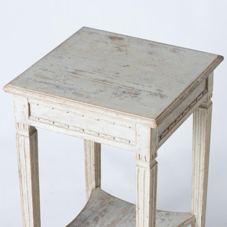This elegant table from the Gustavian period has refined details, including carvings around the apron, and distinctly reeded legs framing the indented bottom shelf. The pale cream paint surface is original. The table is an ideal size to fit in many