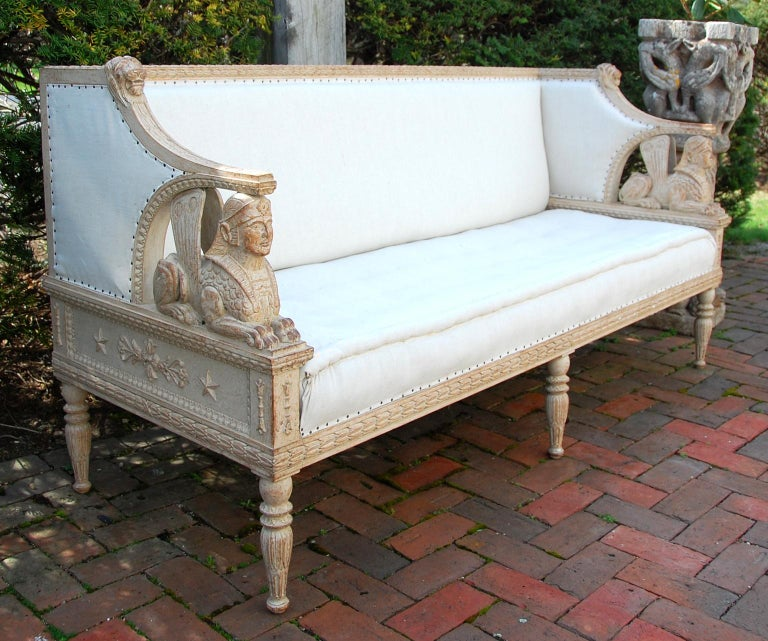 Swedish Gustavian style mid-19th century carved beechwood sofa, full bodied hand carved sphinx support the arms. Hand carved lion heads accent the top leaf carved backrail, with extensive carving on most beech surfaces, off white linen upholstery.