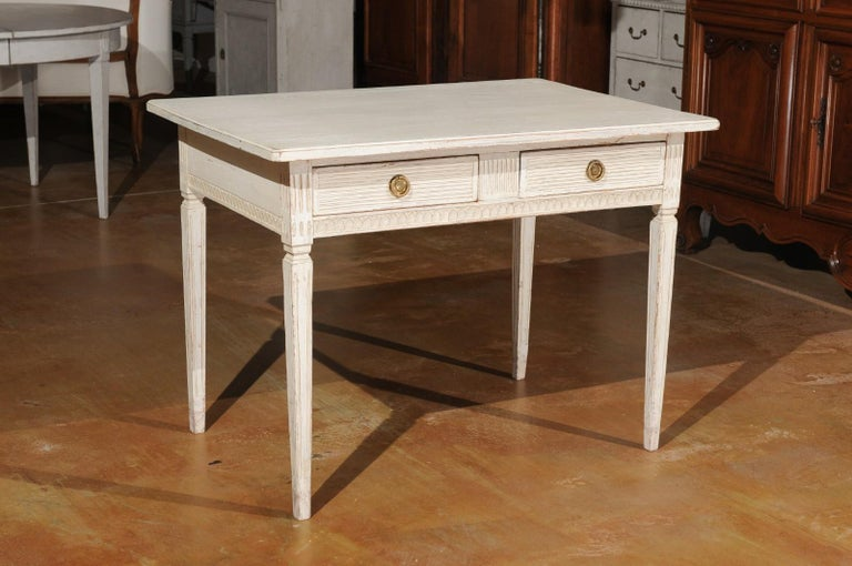 A Swedish Gustavian style painted desk from the mid-19th century, with two drawers, fluted motifs and tapered legs. Created in Sweden during the 1850s, this Gustavian style painted desk features a rectangular top sitting above two drawers adorned