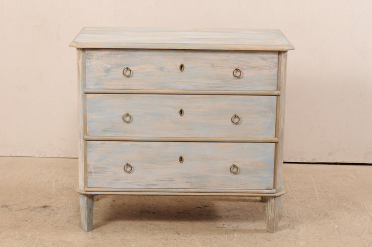 A Swedish painted wood three drawer chest from the mid-19th century. This antique chest from Sweden has been designed in typical Gustavian style, featuring a simple, clean design with slanted side posts and feet, and each top forward corner