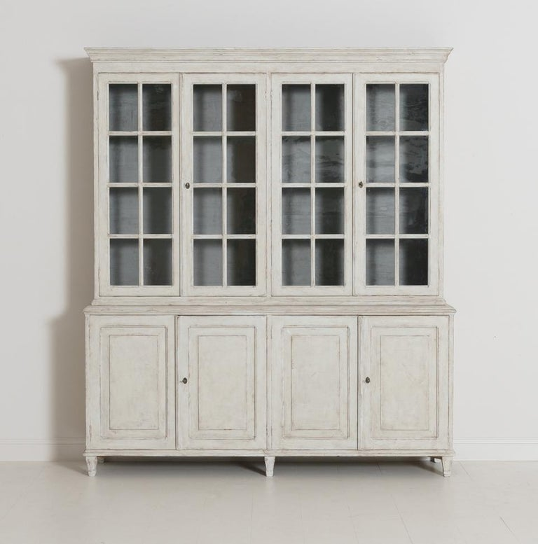 A beautiful Swedish Gustavian Style four-door painted vitrine cabinet. This bookcase is made in two parts. The upper section has three fixed shelves behind original glass doors. The shelf depth is 10 inches. The distance between shelves starting