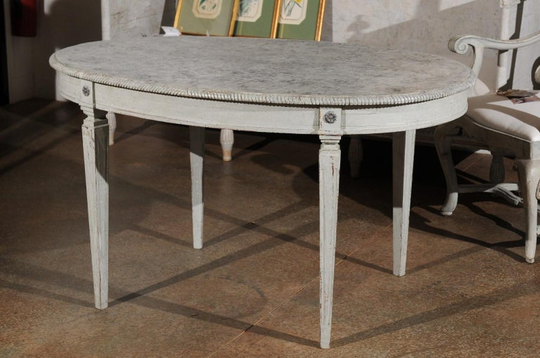 A Swedish grey painted Gustavian style wooden table from the late 19th century, with oval marbleized top, tapered legs, rosettes and distressed finish. Born in Sweden during the later years of the 19th century, this exquisite oval table features the