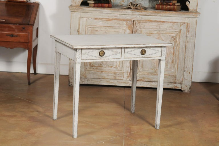A Swedish Gustavian Style painted wood desk from the 20th century, with two drawers, diamond motifs and carved rosettes. Born in Sweden during the 20th century, this painted desk features a rectangular top sitting above two drawers, each carved with
