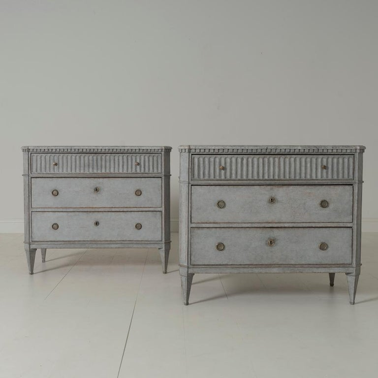 A beautiful pair of Swedish commodes in the Gustavian style with hand painted marbleized tops. There is dentil molding around the top with a fluted top drawer. Chalky gray paint. Three drawers, canted and fluted corner posts, and tapered and fluted