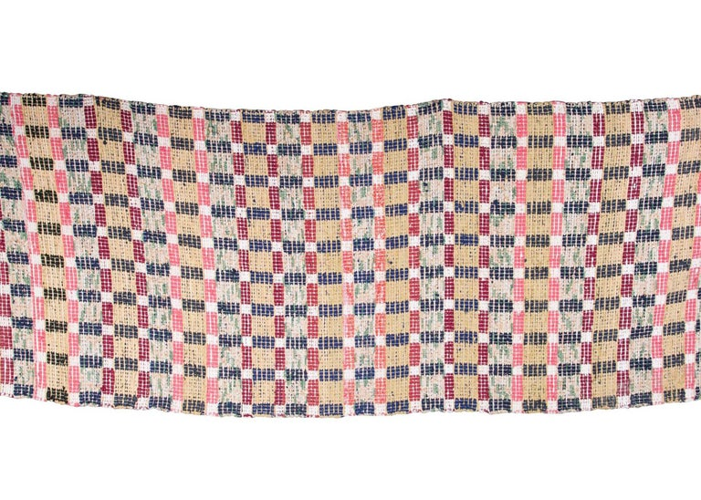 A decorative handmade Swedish rug in a blocked square design, with accents of raspberry, cream and black.
