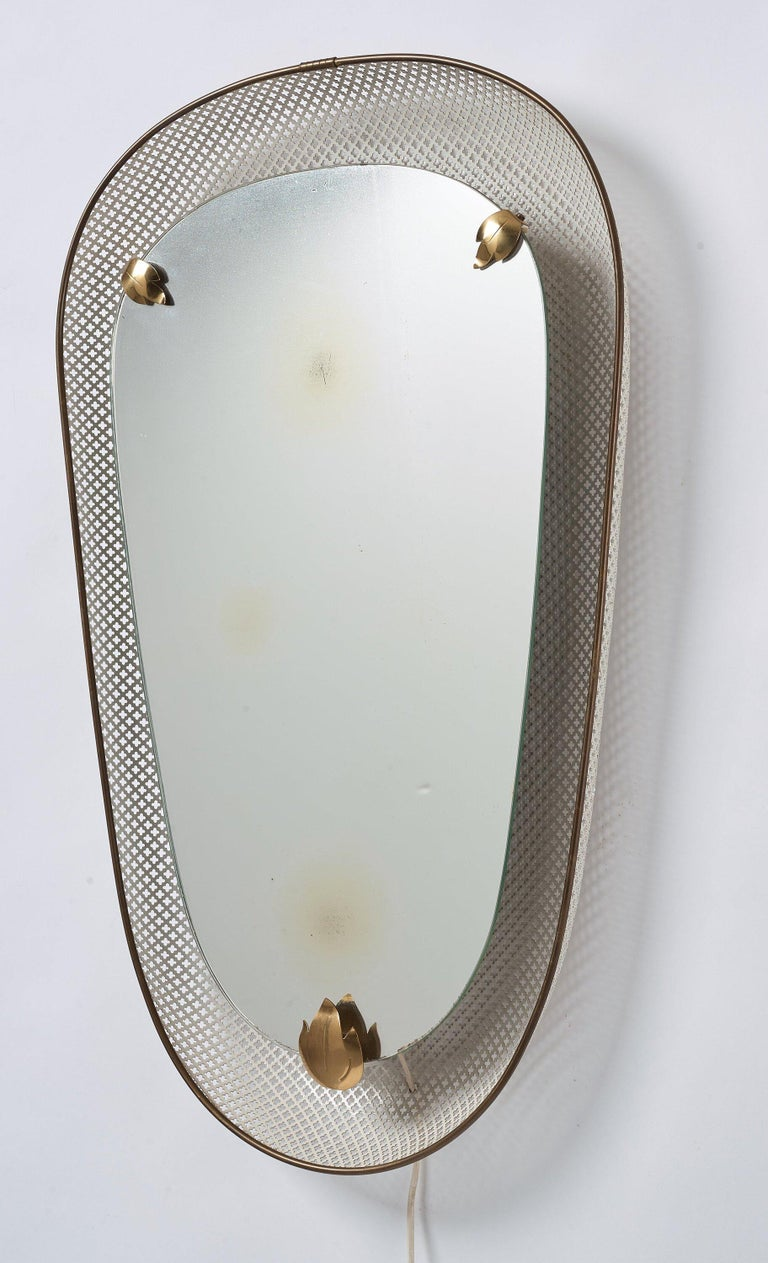 An organically shaped illuminated wall mirror. Designed and produced in Sweden, 1940s. Perforated and lacquered metal gives the work a light expression.   Other designers of the period include Paolo Buffa, Jean Royere, Josef Frank, Franco Albini,