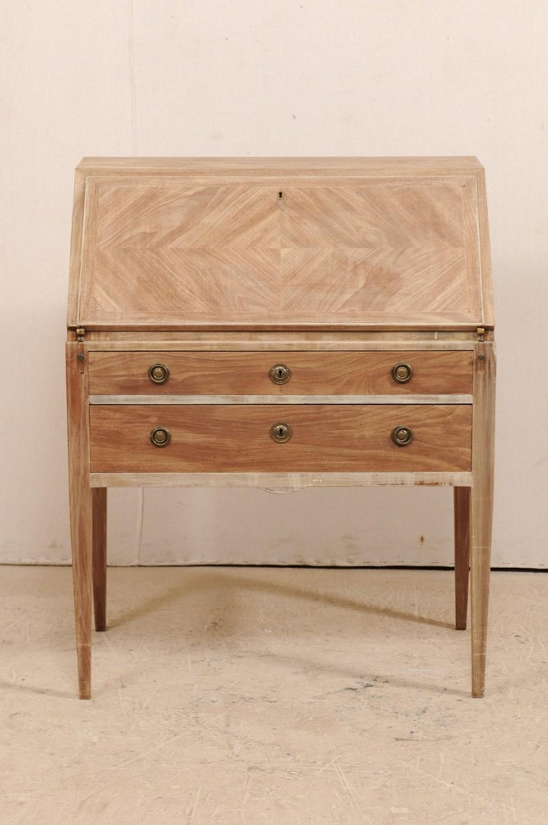 A Swedish drop-leaf secretary from the mid-20th century. This Swedish slant-top writing desk, with it's simplistic and clean design, features a top leaf which folds down to reveal smaller drawers an open, center cubby hole. When this leaf is opened,