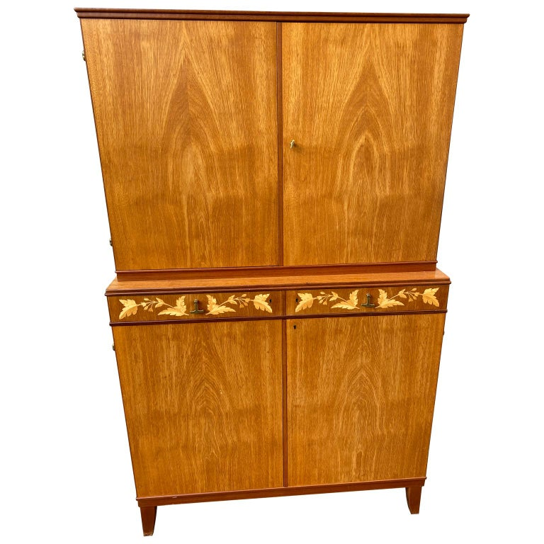 A sharp looking Swedish-made cabinet by J.O. Carlssons. The cabinet has two drawers with original brass hardward and citrus veneer inlaid flower decorations. It is in good sturdy condition. Lower part of the cabinet has options for two shelves,