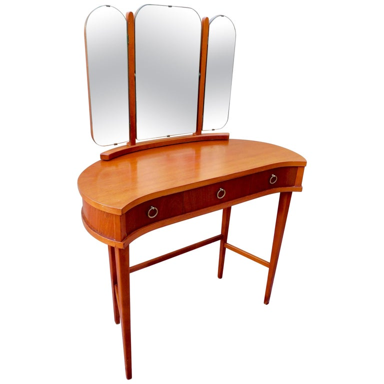 Swedish Mid-Century Modern vanity table. With tilting triptych mirror. Three drawers, the center one with beautifully finished pullout / pull-out interior. In great original condition with some light wear.