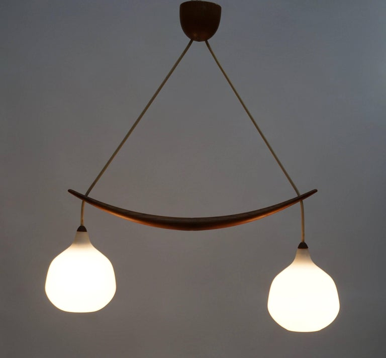Pendant in oak and opaline glass. The lamp features two hanging glass spheres, divided by a carefully carved oak stick. Measures: Height 65 cm. Width 75 cm.