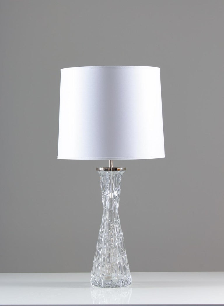 A pair of impressive table lamps in crystal glass model RD 1477 by Carl Fagerlund for Orrefors, Sweden. The base is made of crystal glass and reminds of frozen water. The chrome details add to the feeling of Frost and ice that is significant for the