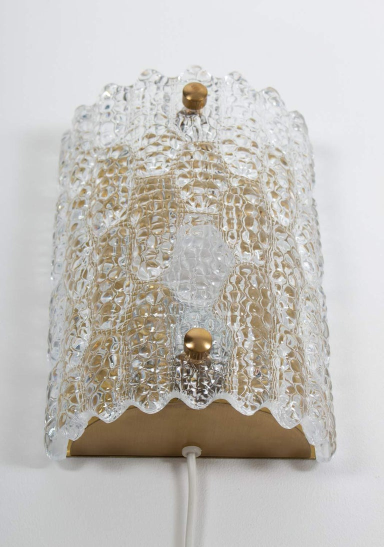 Beautiful wall lamps by Carl Fagerlund for Orrefors, Sweden. The lamps consist of a crystal glass block fixtured on a brass bottom. 5 pieces available.