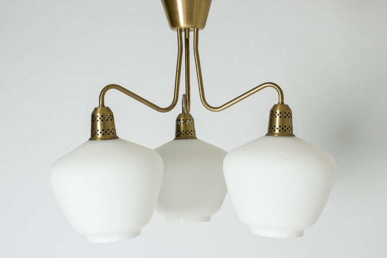 Elegant Swedish midcentury chandelier, with a brass frame and large, opaline glass shades. Beautifully cut out pattern in the brass light bulb holders.