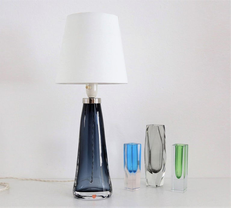 Beautiful table lamp made in Sweden during the 1960s, design Carl Fagerlund, produced by Orrefors. The stunning shiny blue crystal glass is in very good condition. The lamp has been re-wired with new fabric caord and on-off switch. The lamp shade