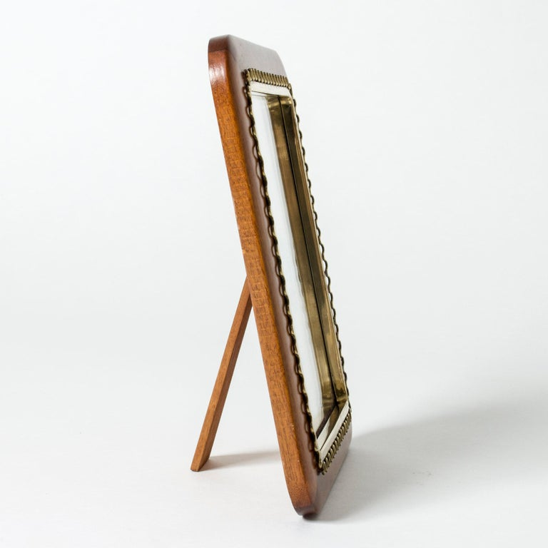 Lovely Swedish midcentury table mirror. Made with a mahogany frame with rounded corners, decorated with a beautiful wave-shaped brass rim.