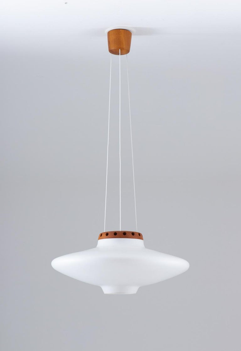 A pendant by Uno and Östen Kristiansson for Luxus, 1950s. This lamp features a large sphere in frosted opaline glass, held by a teak piece with small holes around it that lets the light out in a beautiful way against the ceiling. Three wires are