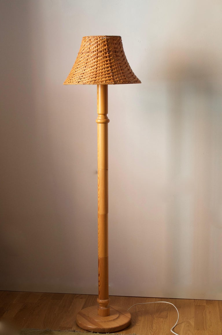A floor lamp designed and produced in Sweden, 1970s. In solid pine. Assorted vintage rattan lampshade.