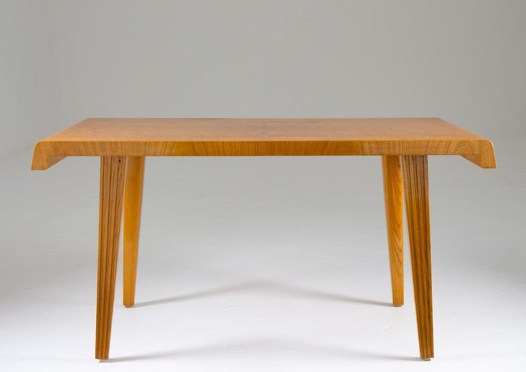 Beautiful coffee or side table made of elm and elm root veneer. This table is a superb example of the great designs during the Swedish modern era. It consists of a beautiful table top, tilted in the ends and with beautiful elm root inlays in the